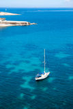 Sailing boat in blue water bay Stock Photos