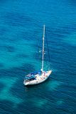 Sailing boat in blue water bay Stock Photo