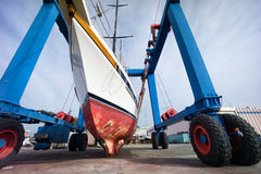 Sailing boat in boatyard on  a crane Royalty Free Stock Images
