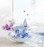 Sailing Boat in a cup of tea with birds. Flying around Stock Image