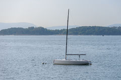 Sailing boat with deflated sails moored near the shore Stock Photos