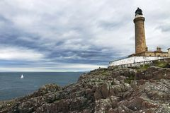 A sailing boat in front of the Ardnamurchan Lighthouse on the west coast of Scotland royalty free stock photo