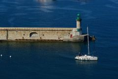 Sailing boat in front of a green lighthouse