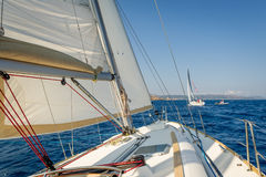 Sailing boat going fast on she's sails, view from the cockpit to bow. Royalty Free Stock Photography