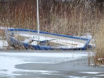 A sailing boat has been forgotten in ice. Winter is coming and the owner has left the boat in bushes Stock Photos