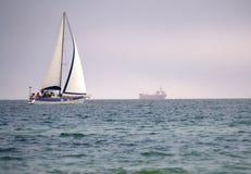 Sailing boat the high seas. Sailing  boat and cargo ship at the horizon.Picture taken on May 1st,2014 at  Varna bay,Bulgaria,Black sea Stock Photo