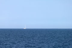 Sailing boat by the horizon Royalty Free Stock Photo