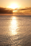 Sailing boat on horizon bathed in sun's rays. Sailing boat on the horizon is bathed in the sun's rays at sunrise Royalty Free Stock Image