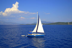 Sailing boat Ionian islands off shore. White boat in deep blue scenery of Ionian Sea scenery,Greece Stock Image