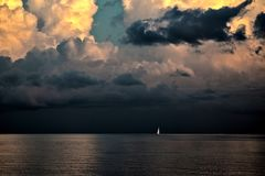 Sailing boat in Key West. The picture was taken from a cruise ship. We liked the loneliness of the sail in front of the ominous clouds royalty free stock image