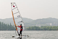 Sailing boat in the lake. The picture was taken on May 4th,2012 at the West Lake,Hangzhou,China. A boy athlete was practising with his sailing boat Royalty Free Stock Photos