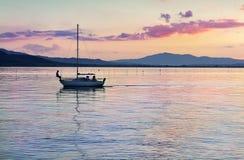 Sailing boat on the lake at sunset Stock Photo