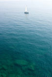 Sailing boat in limpid water royalty free stock photos