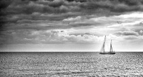Sailing boat. Lit by sun rays on a calm sea sailing towards clouds Royalty Free Stock Images