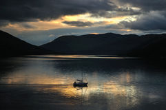 Sailing boat on Loch Earn in scottish Highlands. View on the boat on Loch Earn in scottish Highlands during colored sunset Royalty Free Stock Photo