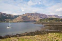 Sailing boat on Loch Leven Scottish lake Scotland Scottish Highlands with mountains Royalty Free Stock Image