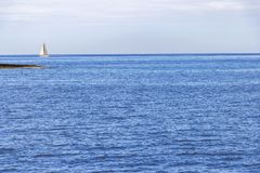 A sailing boat in the Maltese Mediterranean water of Marsamxett Harbor. Deep blue seascape with a sailing boat in the Maltese Mediterranean water of Marsamxett Royalty Free Stock Photos