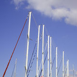 Sailing boat masts in a row. Against the blue sky Stock Image