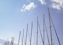 Sailing boat masts. A row of white sailing boat masts against a blue summer sky Royalty Free Stock Image