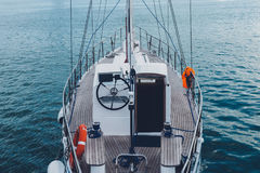 Sailing Boat Moored To Pier In Harbor Walk To Sea Water Transport Concept. Beautiful white sailing yacht moored to the shore in the harbor against the backdrop royalty free stock image