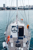 Sailing Boat Moored To Pier In Harbor Walk To Sea Water Transport Concept. Beautiful white sailing yacht moored to the shore in the harbor against the backdrop stock photography