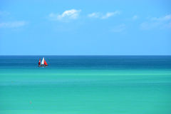 Sailing boat on multicolored sea Royalty Free Stock Photos