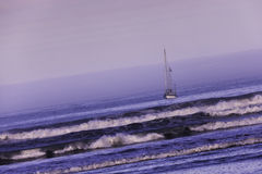 Sailing boat on the ocean at dawn. Royalty Free Stock Image