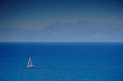 Sailing boat at an open sea stock photography