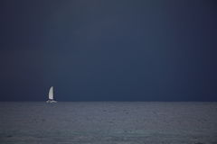 Sailing boat voyage by storm brewing. A single sailing boat voyaging on the yet calm sea by a storm brewing (Australia&#x29 Stock Images
