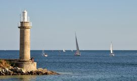 SAILING BOAT PAST LIGHTHOUSE, FRANCE Stock Image