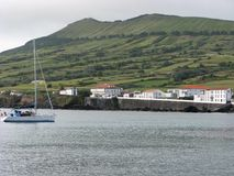 Sailing boat at Praia on Graciosa island, The Azores. Sailing boat in front of white houses and a headland at Praia on Graciosa island, The Azores stock photos