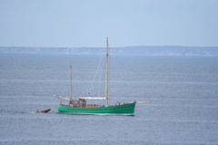 Sailing boat pulling dingy. Sailing boat with sails down pulling dingy royalty free stock images