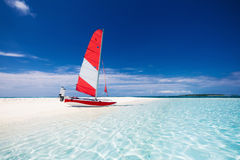 Sailing boat with red sail on a beach of deserted tropical islan. D with shallow blue water Stock Image