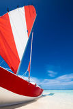 Sailing boat with red sail on a beach of deserted tropical islan. D with shallow blue water Royalty Free Stock Photography