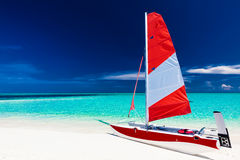 Sailing boat with red sail on a beach of deserted tropical islan Royalty Free Stock Photos
