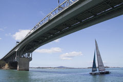 Sailing boat riding throught Auckland Harbour Bridge, New Zealand Royalty Free Stock Photos