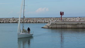 Sailing boat sails to the pier. Stock Image