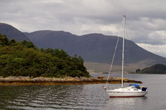 Sailing boat on scottish lake. Sailing boat on a lake in the Highlands, Scotland Royalty Free Stock Photo