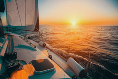 Sailing boat in the sea during awesome sunset. Royalty Free Stock Photography