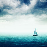 Sailing boat on the sea. Sailing boat on Blue sea with heavy storm clouds, conceptual image of uncertain future Royalty Free Stock Photos