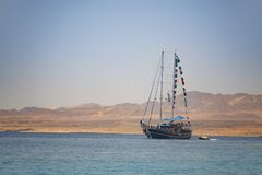 Sailing Boat at A Sea Journey with Mountains Beach in Background, Pirates Look royalty free stock photo