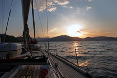 Sailing boat in the sea at sunset royalty free stock photography