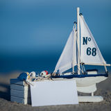 Sailing boat and seashell sand decoration closeup Royalty Free Stock Photos