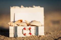 Sailing boat and seashell sand decoration closeup Stock Photos