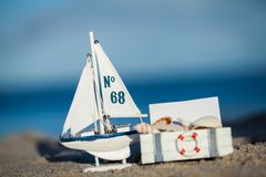 Sailing boat and seashell in sand decoration closeup Stock Photos