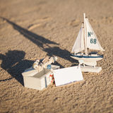 Sailing boat and seashell in sand decoration closeup Stock Images
