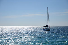 Sailing boat on shimmering sea Royalty Free Stock Photography