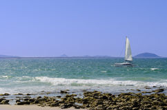 Sailing boat and shore Stock Images