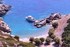 Sailing boat and some people swimming in a bay. At island karpathos greece. summer time Royalty Free Stock Photos