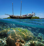 Sailing boat stranded on reef with fish and coral. Over-under split view of an old sailing boat stranded on a reef with shoal of tropical fish and coral under stock photo